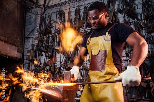 handsome african americam man forging steel next to furnace in dark workshop Canvas Print