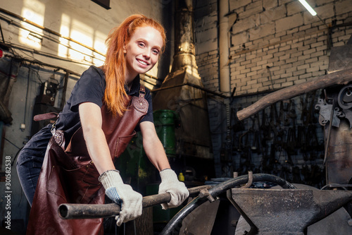 Fotomural redhead ginger woman blacksmith portrait in workshop