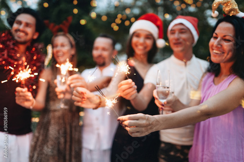 Spoed Fotobehang Kerstmis Group of friends celebrating Christmas with sparkles and champagne