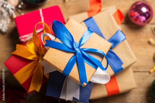 Fotografía  Stack of gifts, Christmas-tree decorations on a wooden background