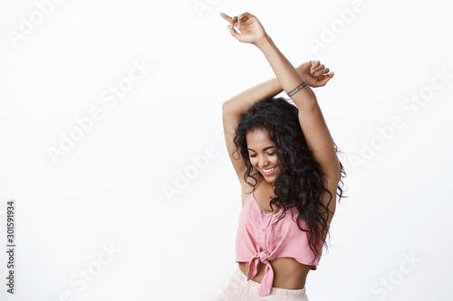 Waist-up shot of attractive african-american curly-haired tattooed woman having fun, dancing enjoying christmas party, raise hands up and smiling enjoying own body, move to rhythm, white background - 301591934