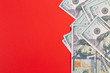 canvas print picture - United States or USA 100 dollar currency on a red background and copy space.  Fake money and financial fraud concept.
