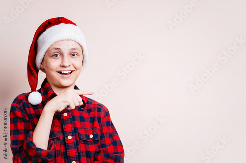 Vászonkép enthusiastic motivated overexcited boy wearing santa claus hat points with index
