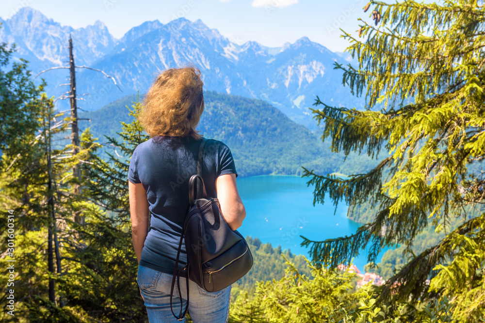 Fototapety, obrazy: Woman looks at Alpine landscape, Bavaria, Germany. Scenic view to Alpsee Lake, tourist place in nature. Adult girl travels in forested mountains in summer. Concept of hiking and trekking in Alps.