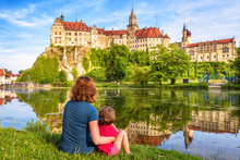Family Sit Near Medieval Sigmaringen Castle, Germany. Young Woman And Her Child Are By River In Summer.