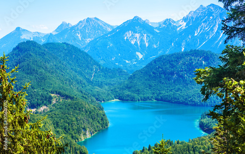Landscape of Alpine mountains, Germany. Panoramic scenic view of nature from above. Perfect landscape with Alpsee lake in summer. Beautiful scenery of Bavarian Alps with green forest and blue peaks.