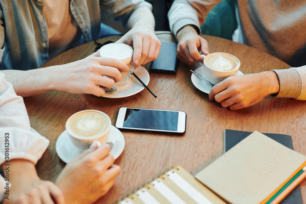 Fototapeta Hands of college friends sitting by wooden table in cafe and having cappuccino