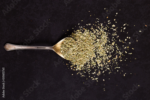 Obraz Crushed oregano scattered in an iron spoon on a black table. Concept, copy space. - fototapety do salonu
