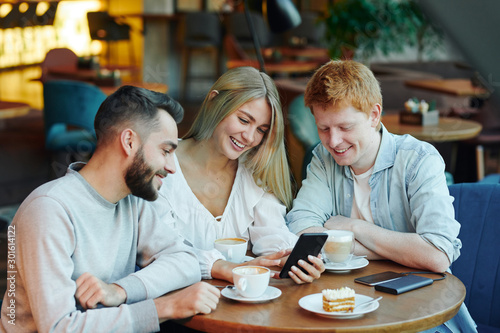 Fototapety, obrazy: Pretty blonde girl and two happy guys scrolling through photos in smartphone