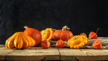 Atristic Autumn Rustic Still Life. Pumpkins With Squash And Physalis On A Rough Burlap And Boards Against A Dark Concrete Wall