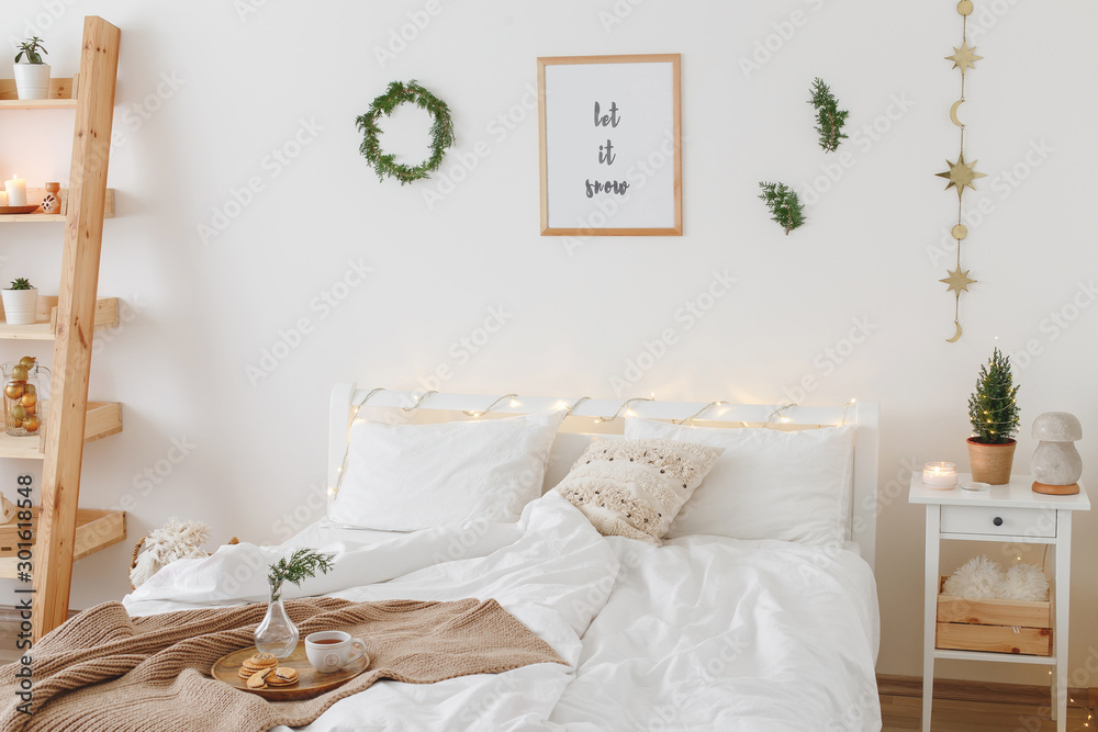 Fototapety, obrazy: New year winter home interior decor. Christmas holiday decorations: little christmas tree, wreath, coniferous twigs, pine branches, led garland lights, blanket. White stylish cozy scandinavian bedroom