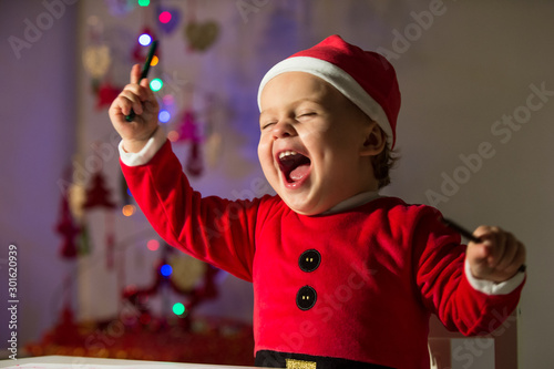 Obraz Little Santa playing with paintings sitting on his stool and writing the letter of the gifts he wants to Santa. - fototapety do salonu