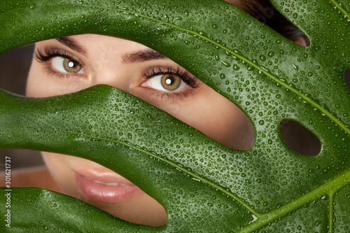 Obraz na plátne Beautiful Woman with long lashes on the background of a leaf of monstera with water droplets