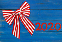 Year 2020 In Bold Red And Large Bow On Antique Rust Blue Wood Background; Message Board With New Year Holiday Concept And Painted Copy Space