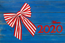 Welcome Year 2020 In Bold Red And Large Bow On Antique Rust Blue Wood Background; Message Board With New Year Holiday Concept And Painted Copy Space