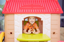 Happy Little Boy Playing In A Playhouse
