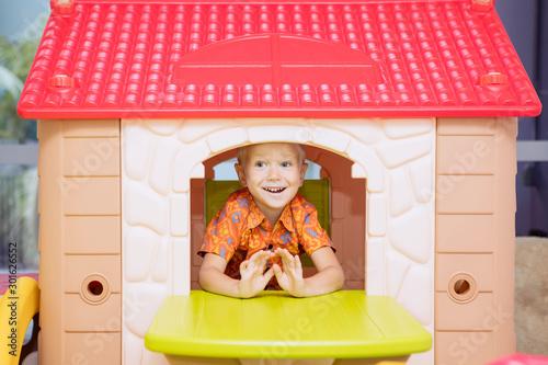 Fotografia, Obraz Happy little boy playing in a playhouse