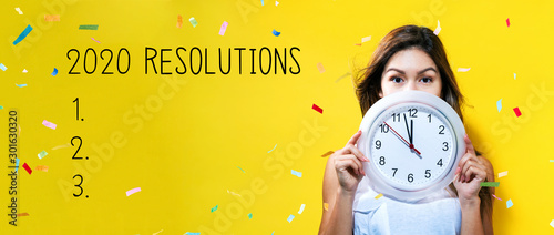 Canvastavla  2020 Resolutions with young woman holding a clock showing nearly 12