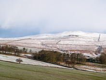 A Skiff Of Snow Covers The High Fells And Hills Of Yorkshire, England Under A Leaden Sky With Green Fields In The Foreground.