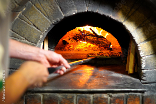 Canvas Prints Pizzeria Pizza maker hands take out pizza from stone oven