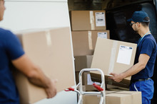 Manual Worker Preparing Packages For Shipment And Loading Them In Delivery Van.