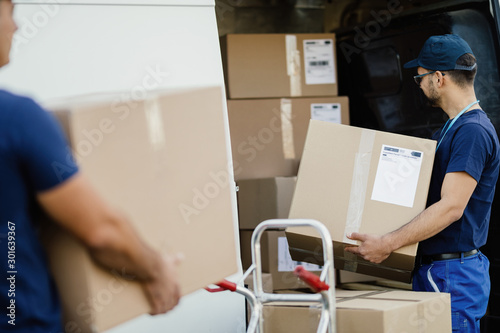 Fotomural Manual worker preparing packages for shipment and loading them in delivery van