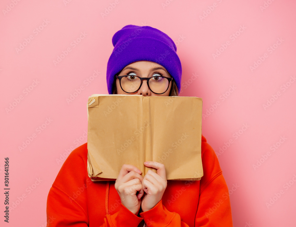 Fototapeta Style girl in orange hoodie and purple hat with book on pink background