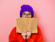 Style girl in orange hoodie and purple hat with book on pink background