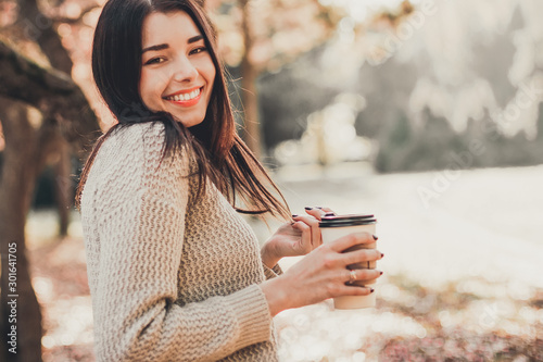 Beautiful woman drink coffee and posing for the camera in autumn park. - 301641705