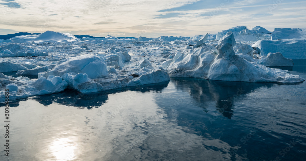 Fototapeta Drone photo of Iceberg and ice from glacier in arctic nature landscape on Greenland. Aerial photo drone photo of icebergs in Ilulissat icefjord. Affected by climate change and global warming.