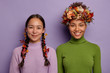 canvas print picture - Horizontal view of glad women stand next to each other, express positive emotions, decorate hair with autumn attributes, prepare to celebrate seasonal holiday, isolated over purple background