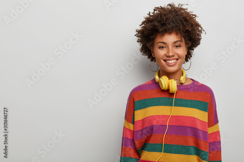 Energetic enthusiastic woman with curly crisp hair, listens music via headset, s Canvas Print