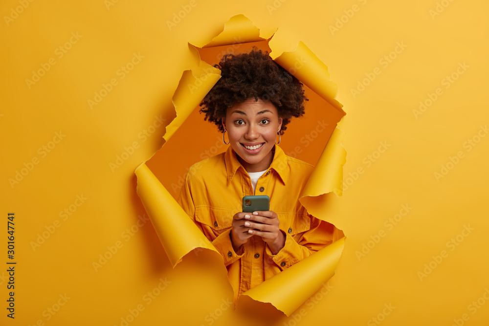 Fototapeta Happy curly haired student laughs at funny joke in social networks, smiles toothily, plays game online on modern cellphone, dressed in stylish outfit, stands in ripped hole background, yellow color