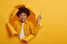 Studio Shot Of Positive African American Woman Points Finger To Copy Space Above, Excited By Good Information, Smiles Pleasantly, Wears Yellow Jacket, Stands In Ripped Paper Hole. Advertisement