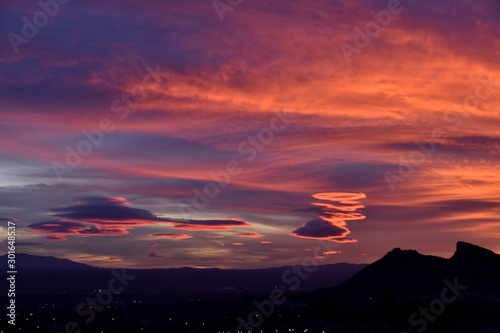 Fotobehang Baksteen splendid autumn sunset with different types and colors of lenticular clouds