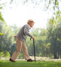 Senior Man Walking With A Cane In A Park