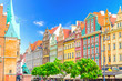 Row of colorful buildings with multicolored facade and wall of Old Town Hall building on cobblestone Rynek Market Square with green trees in old town historical city centre of Wroclaw, Poland