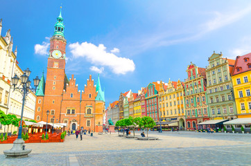 Old Town Hall building, row of colorful buildings with multicolored facade and street lamp on cobblestone Rynek Market Square in old town historical city centre of Wroclaw, Poland