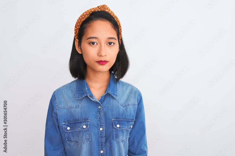 Fototapeta Young beautiful chinese woman wearing denim shirt standing over isolated white background with serious expression on face. Simple and natural looking at the camera.