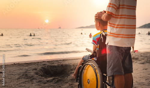 Foto auf Gartenposter Cappuccino Father and Asian special child on wheelchair is happily on the beach, Dad and son spend holiday to travel and learning about nature around the sea,Life in the education age,Happy disabled kid concept.