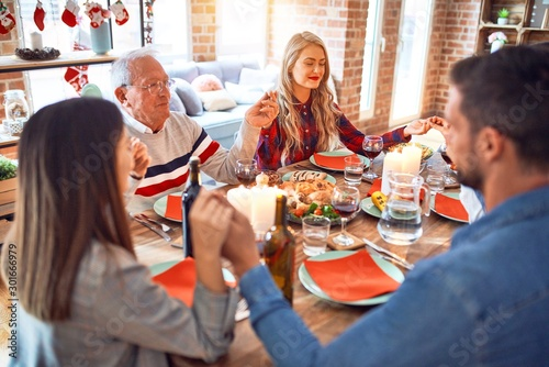 Beautiful family meeting smiling happy and confident. Praying taking hands before eating roasted turkey celebrating Christmas at home