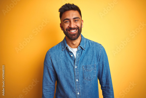 Young indian man wearing denim shirt standing over isolated yellow background with a happy and cool smile on face Fototapete