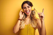 Young beautiful woman wearing headphones over yellow isolated background very happy pointing with hand and finger to the side