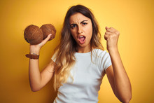 Young Beautiful Woman Holding Coconut Over Yellow Isolated Background Annoyed And Frustrated Shouting With Anger, Crazy And Yelling With Raised Hand, Anger Concept