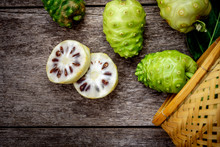 Close Up Morinda Citrifolia (Common Name As Noni Fruits, Indian Mulberry, Cheese Fruit) In Basket With Horizon Sliced Isolated On Rustic Wooden Table Background. Top View. Dark Tone. Vintage Style.