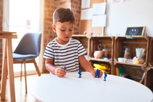 Beautiful Toddler Boy Playing With Figurine Army Soldiers At Kindergarten