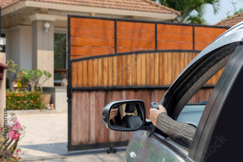 Fotomural Woman hand using remote controller to open the automatic gate when arrived home