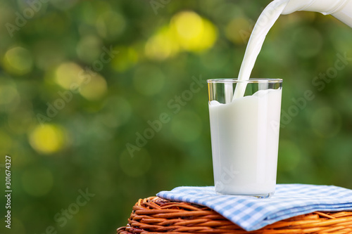 milk from jug pouring into glass Canvas Print