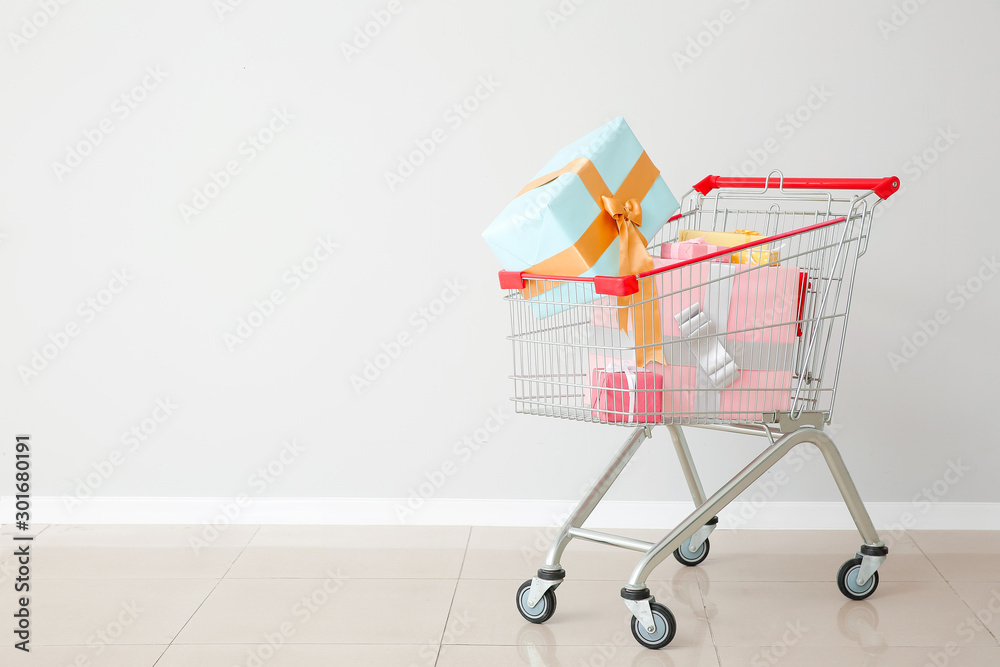 Fototapeta Shopping cart with gifts near light wall