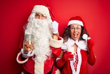 Couple Wearing Santa Costume Holding Jar Of Cookies And Milk Over Isolated Red Background Screaming Proud And Celebrating Victory And Success Very Excited, Cheering Emotion